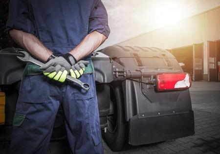 Foto de Broken Truck Problem. Semi Trucks Mechanic with Large Wrench Looking For Ideas How to Fix the Problem. - Imagen libre de derechos