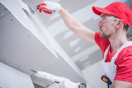 Photo pour Residential Remodeling Drywall Patching. Caucasian Contractor in His 30s. Construction Theme. - image libre de droit