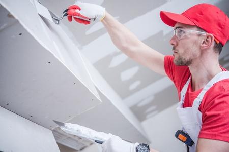Foto de Residential Remodeling Drywall Patching. Caucasian Contractor in His 30s. Construction Theme. - Imagen libre de derechos