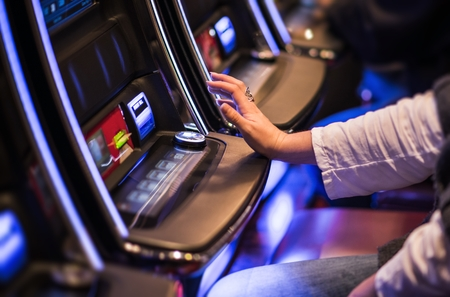 Foto de Casino Video Slots Game Playing. Caucasian Woman Feeling Lucky in the Vegas Casino. - Imagen libre de derechos