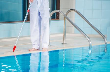 Foto de Interior Swimming Pool Cleaning. Caucasian Worker Cleaning Ceramic Sides of the Pool.  - Imagen libre de derechos