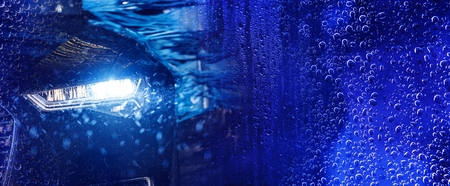 Foto per Modern Car Wash Banner Concept Background with Car in the Automatic Brush Washer. Deep Blue Color Grading. - Immagine Royalty Free