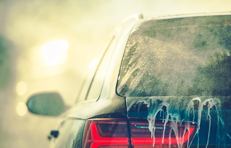 Photo pour Cleaning Vehicle in the Car Wash. Closeup Photo. Auto Body Covered by Washing Detergent. - image libre de droit