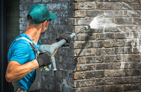 Foto de House Brick Wall Washing Using Pressure Washer. Caucasian Worker in His 30s. - Imagen libre de derechos