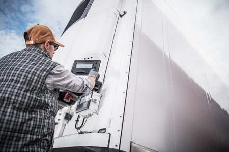 Photo pour Refrigerated Semitrailer Cargo. Adjusting Temperature by Caucasian Truck Driver. - image libre de droit