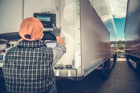Foto de Trucker Adjusting Temperature in the Refrigerated Semitrailer. Transportation Industry Theme. - Imagen libre de derechos