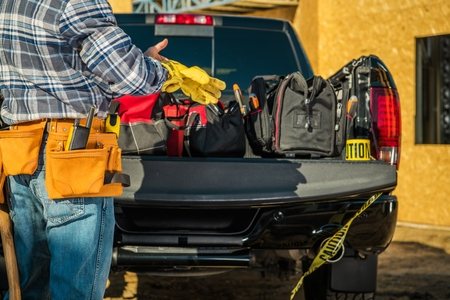 Foto de Construction Business Industry. Caucasian Contractor Worker Preparing Himself For the Job by Wearing Safety Gloves in Front of His Pickup Truck Full of Necessary Tools. - Imagen libre de derechos