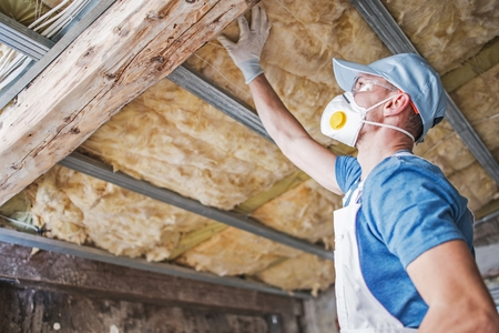 Foto de Old Roof Insulation. Caucasian Construction Worker in His 30s Inspecting Aged Roof and Mineral Wool Insulator. - Imagen libre de derechos