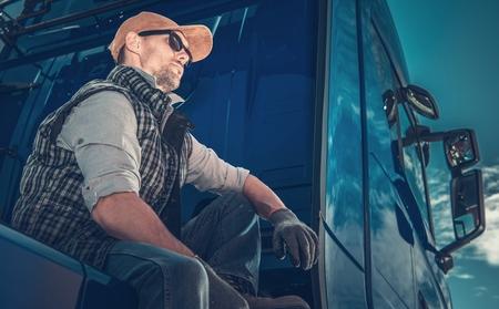Photo pour Caucasian Truck Driver Wearing Sunglasses Taking Short Break on the Truck Stop. - image libre de droit