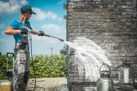 Foto de Brick House Wall Pressure Washing with Special Cleaning Detergent. Caucasian Men in His 30s. Taking Care of the Building Elevation. - Imagen libre de derechos