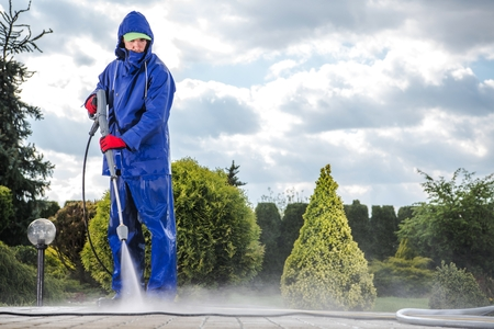 Foto per Men Wearing Industrial Wet Coat with Pressure Washer Cleaning Driveway. - Immagine Royalty Free