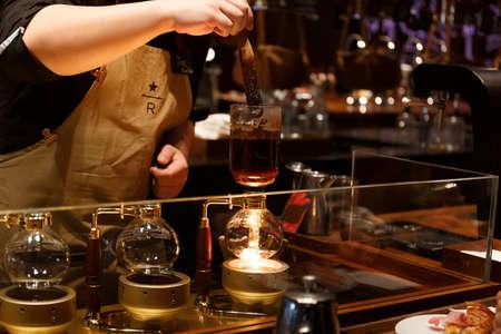 Foto de Shanghai, China – November 9, 2019: A barista prepares coffee in the 2nd Biggest Starbucks Reserve Roastery in the World - Imagen libre de derechos