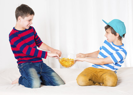 Photo pour two young boys in bed and fighting over a bowl of potato chips - image libre de droit