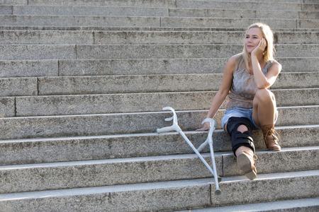 Foto de blonde woman with crutches sitting on stairs - Imagen libre de derechos