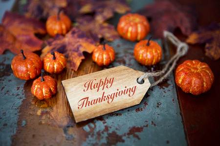 Foto de Happy Thanksgiving on wooden tag with pumpkins and leaves - Imagen libre de derechos