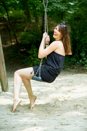 young brunette woman sitting on a swing at a playground