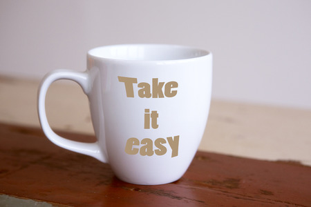 Photo pour white cup with the words Take It Easy on red wooden table - image libre de droit
