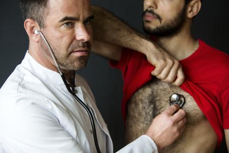 Foto de handsome doctor with a stethoscope listening to patients heartbeat - Imagen libre de derechos