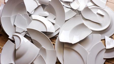 Foto de many white broken plates on a wooden floor - Imagen libre de derechos