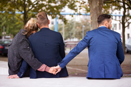 Foto de couple sitting on bench and hugging while the woman holding hands with another man - Imagen libre de derechos