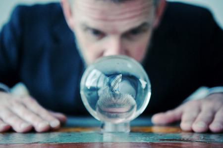 Photo pour closeup of businessman looking at glass ball on table - image libre de droit