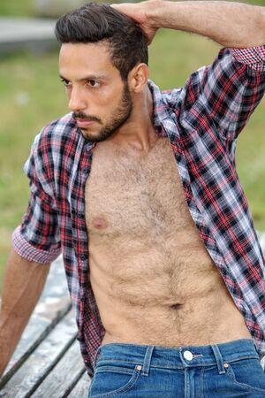 Foto de portrait of sexy bearded man with open shirt sitting outdoors - Imagen libre de derechos