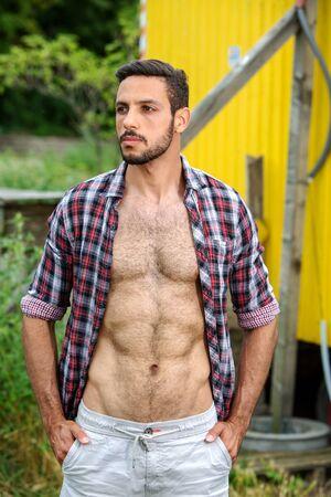 Foto de portrait of handsome bearded man standing outdoors with open shirt - Imagen libre de derechos
