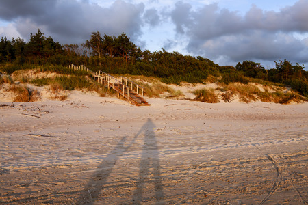 Shadows of two figures - father and son holding hands - in the beach sand and trees, sunset, dramatic sky with clouds, visible coast line