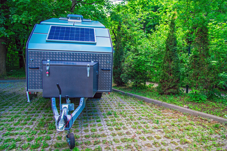 Photo pour Solar panel is fixed on the tourist trailer. Off-road trailer stands in the parking lot on the background of thick green foliage. Copy space. - image libre de droit