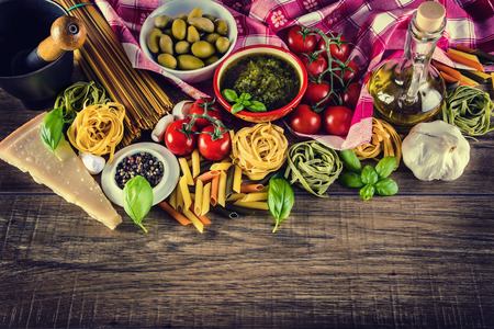 Foto de Italian and Mediterranean food ingredients on old wooden background.spaghetti olives basil cherry tomato pesto pasta garlic pepper olive oil and mortar. - Imagen libre de derechos