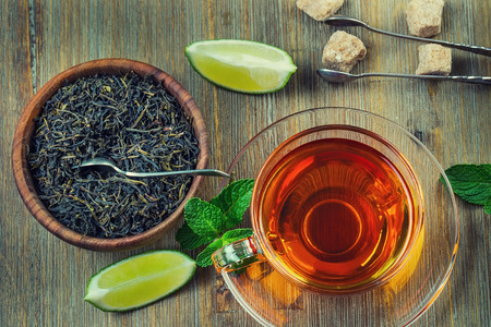 Photo for Tea in a glass cup, mint leaves, dried tea, sliced lime, cane brown sugar - Royalty Free Image