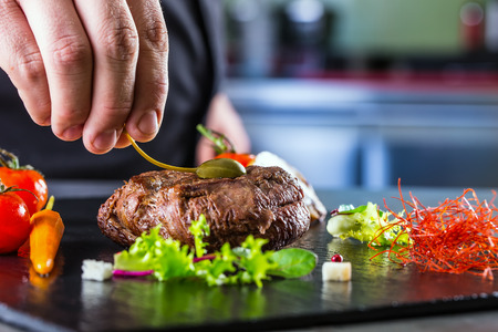 Foto de Chef in hotel or restaurant kitchen cooking only hands. Prepared beef steak with vegetable decoration - Imagen libre de derechos