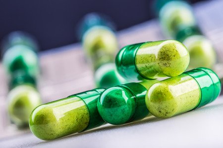 Foto de Pills. Tablets. Capsule. Heap of pills. Medical background. Close-up of pile of yellow green tablets - capsule - Imagen libre de derechos