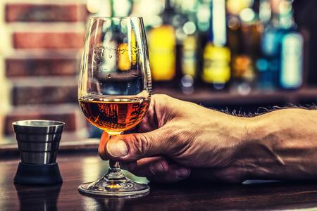 Foto de Alcoholism. Hand alcoholic and drink the distillate brandy or cognac. - Imagen libre de derechos