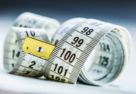 Foto per Curved measuring tape. Measuring tape of the tailor. Closeup view of white measuring tape - Immagine Royalty Free