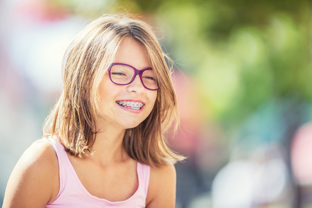 Photo pour Happy smiling girl with dental braces and glasses. Young cute caucasian blond girl wearing teeth braces and glasses. - image libre de droit