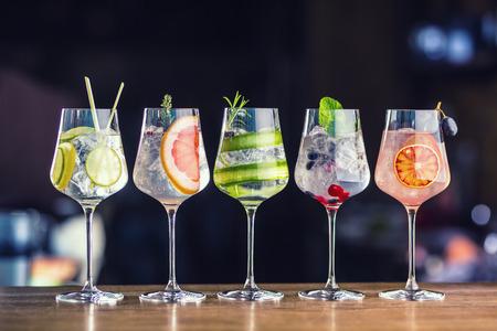 Foto de Five colorful gin tonic cocktails in wine glasses on bar counter in pup or restaurant.  - Imagen libre de derechos