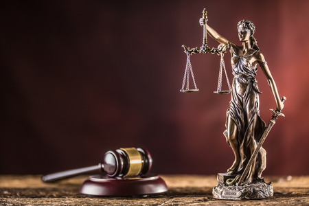 Foto de Lady Justicia holding sword and scale bronze figurine with judge hammer on wooden table. - Imagen libre de derechos