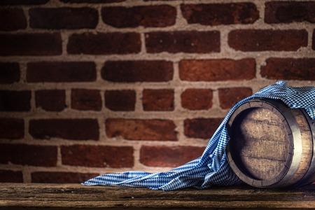 Foto de Oktoberfest wooden barrel and blue tablecloth on rustic oak table. - Imagen libre de derechos