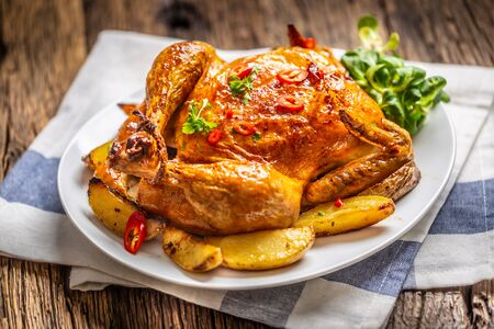 Photo for Roasted chicken and american potatoes with chili peppers and herbs. - Royalty Free Image