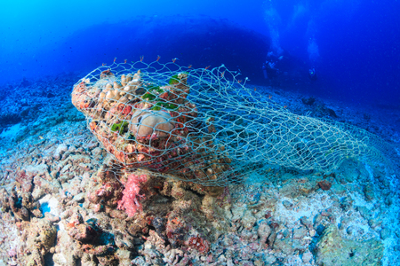 Photo pour An abandoned Ghost fishing net stuck on a tropical coral reef - image libre de droit