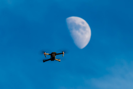 Foto de A consumer quadcopter camera drone hovering with a blue sky and the moon behind - Imagen libre de derechos