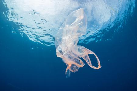 Foto de Plastic pollution:- A discarded plastic bag floats in a clear, blue water, tropical ocean - Imagen libre de derechos