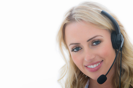 Photo pour Attractive Young Business Woman Using a Telephone Headset Calling Clients Against A White Background - image libre de droit