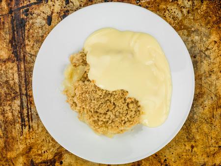 Foto de Apple Crumble Dessert Served With Hot Custard On A Distressed Oven Tray - Imagen libre de derechos