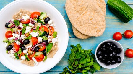 Photo pour Chunky Fresh Healthy Greek Salad With Pitta Bread, Black Olives, Feta Cheese, Red Onions and Mint - image libre de droit