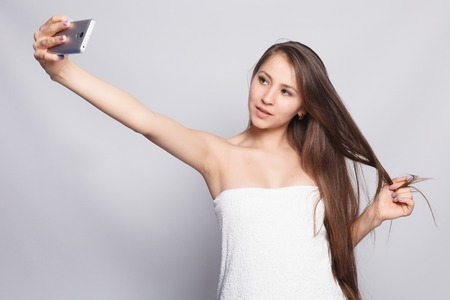 Photo for beauty, skin care and people concept - Spa Woman. Beautiful Girl After Bath Touching Her Face. Perfect Skin. Skincare. Selfie time. Young happy woman taking selfie. Pampering. Treatment - Royalty Free Image
