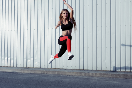 Photo pour Sportswoman jumping and stretching. Full length of healthy female exercising and jumping outdoors. - image libre de droit