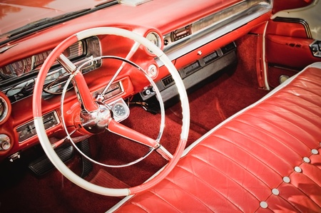 retro styled classic car interior with red leather upholstery and matching dashboard mural