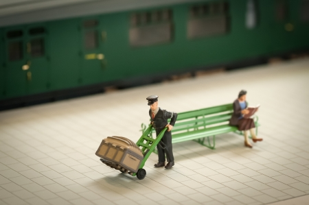 miniature figure of a railway staion porter moving luggage - shallow d.o.f.